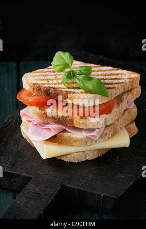 Pain sandwich grillé de grains entiers avec du jambon, du fromage et des tomates sur la planche à découper en bois Banque D'Images