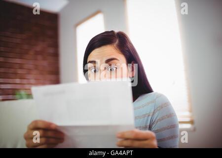 Choqué femme lisant une lettre Banque D'Images