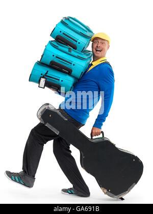 Jeune homme portant une charge de valises et étui à guitare Banque D'Images