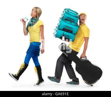 Jeune couple voyageant, femme marche avec une tasse de café, l'homme portant une charge de valises et étui à guitare Banque D'Images