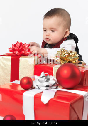 Six mois de l'ouverture des cadeaux de Noël bébé garçon Banque D'Images