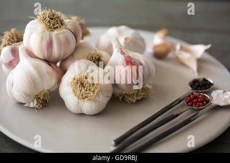 Assiette de l'ail Blubs Rock Rose de l'Himalaya avec le sel et poivre rose et noir. Banque D'Images