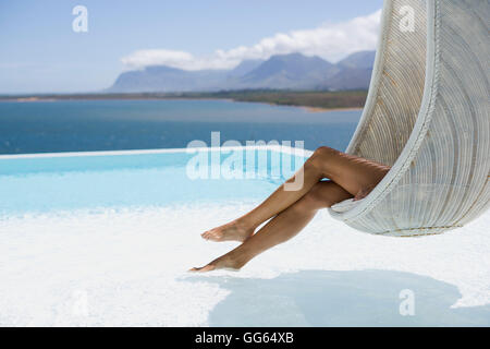 Close-up of a woman relaxing in wicker swing Banque D'Images