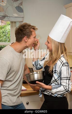 Jeune homme et femme dans une cuisine nourriture d'échantillon à partir d'un bol Banque D'Images