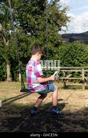 Boy reading in village park, enfant, parc, noir, prairie, arbres, amis, relation, garçon, fille, avant, relaxation, Banque D'Images