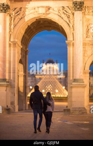 Un couple à l'Arc de triomphe du Carrousel et palais du Louvre au crépuscule, Paris, France Banque D'Images