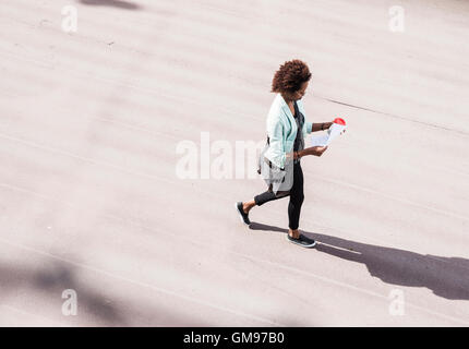 Walking businesswoman looking at document, vu de dessus Banque D'Images