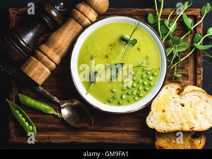 Soupe crème de pois fraîches faites maison dans un bol avec le pain grillé Banque D'Images