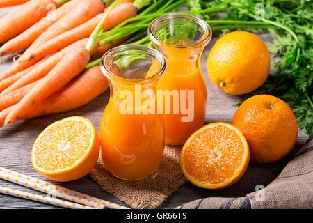 Carotte jus d'orange sur fond de bois Banque D'Images