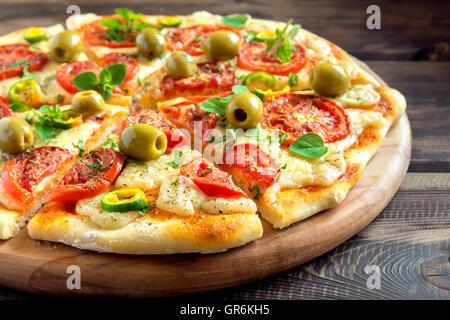 Pizza légumes maison avec des tomates, des olives vertes, le poivre, le basilic, l'origan et de fromage sur la table Banque D'Images