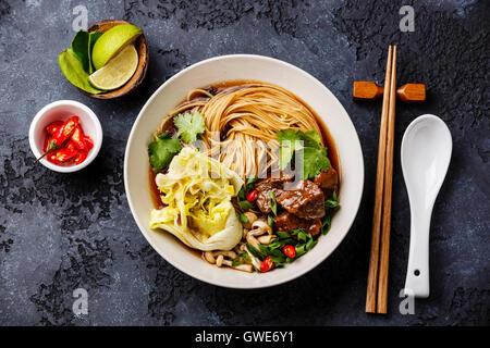 Nouilles asiatiques épicés dans un bouillon de boeuf sur fond sombre Banque D'Images