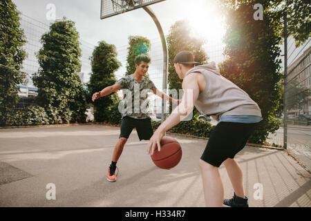 Jeunes amis jouant au basket-ball ensemble, garçon en face de blocage net et autres dribbler le ballon sur une cour. Banque D'Images