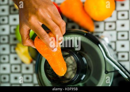 Libre de mains à l'aide de l'insertion, jus de carotte dans la machine, le mode de vie sain concept. Banque D'Images