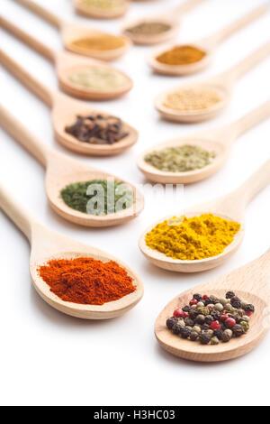 Épices diverses dans des cuillères en bois isolé sur fond blanc. Banque D'Images