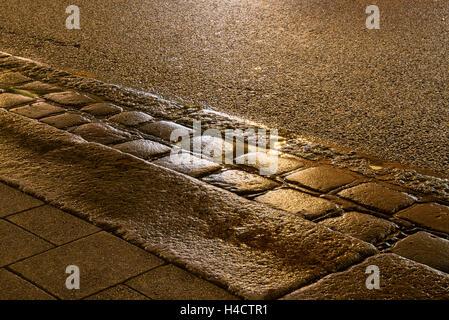 Avec gouttières pavées humides éclairées dans la nuit Banque D'Images