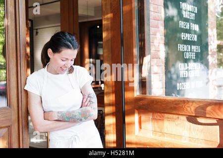 Portrait d'une femme portant un tablier blanc avec les bras croisés dans une porte, les tatouages sur son bras gauche. Banque D'Images