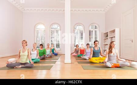 Groupe de personnes dans un studio de yoga sitting in Lotus pose Banque D'Images
