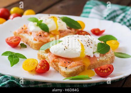 Sandwich avec les oeufs pochés avec du saumon et fromage à la crème. Banque D'Images