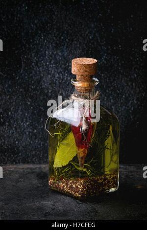 Bouteille de verre d'huile d'olive épicée au romarin, Red Hot Chili Peppers et le laurier sur fond texturé noir Banque D'Images