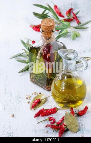 Le flacon en verre et carafe d'huile d'olive épicée au romarin, Red Hot Chili Peppers et le laurier debout avec Banque D'Images