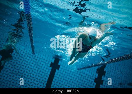 Underwater jeune nageuse natation en piscine. Les jeunes femmes formation nageur dans la piscine. Banque D'Images