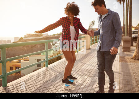 Petit ami fille montrant comment skateboard tout en tenant sa main fermement et lentement sa marche alors qu'elle Banque D'Images