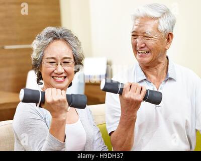 Happy senior couple exerçant à l'aide d'haltères, heureux et souriant Banque D'Images