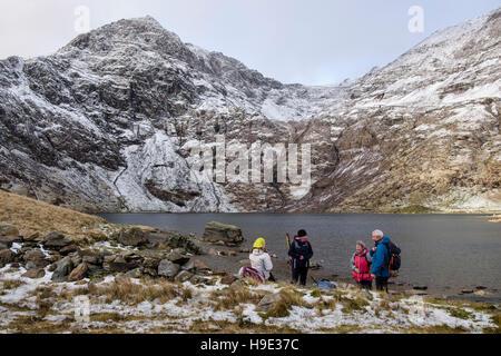 Les randonneurs se reposant par Glaslyn lac ci-dessous Mont Snowdon pic avec la neige en hiver. Le Parc National Banque D'Images
