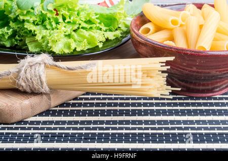 Pâtes alimentaires non cuites et avec une salade verte spaghetti de légumes frais sur la surface de la table de Banque D'Images