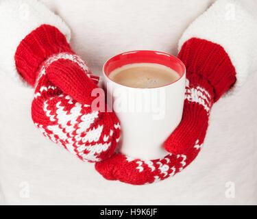 Les mains tenant les mitaines rouges dans du chocolat chaud Banque D'Images