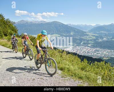 Famille en vtt, chemin de terre, Innsbruck derrière, vallée de l'Inn, Tyrol, Autriche Banque D'Images