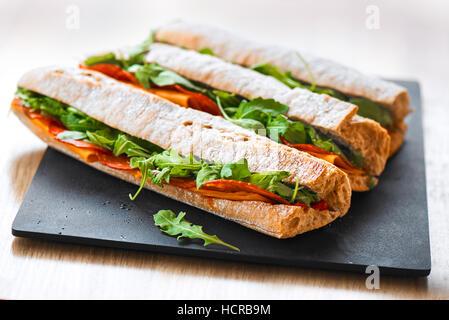 Croûté frais sous-marin sain baguette sandwich au salami, fromage et roquette. Selective focus Banque D'Images