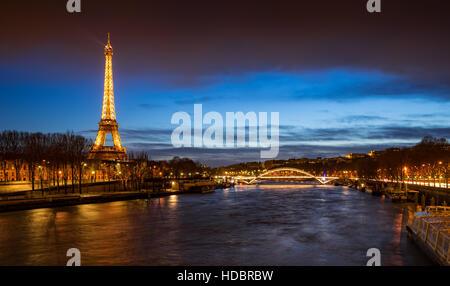 La Tour Eiffel illuminée au crépuscule avec des berges de la Seine et la passerelle Debilly. Paris, France Banque D'Images