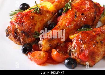 Cuisses de poulet frit à la sauce tomate aux poivrons, olives et romarin sur une plaque blanche, macro horizontale Banque D'Images