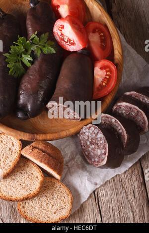 Boudin noir avec de la tomate fraîche sur une plaque close-up vertical Vue de dessus. Banque D'Images