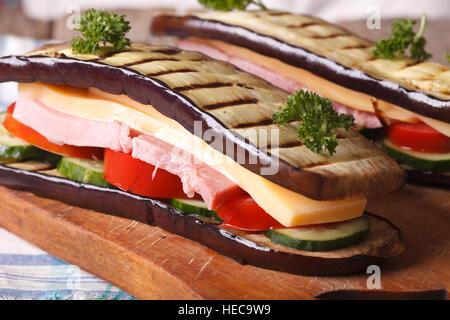 Aubergine sains et délicieux sandwich avec des légumes frais, jambon et fromage close up. Banque D'Images