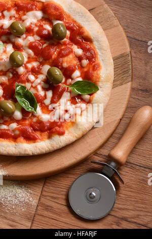 Italian Pizza aux olives vertes sur une planche à découper Banque D'Images