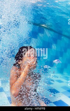 Funny portrait of boy nager et plonger dans la piscine bleu avec plaisir - sauts avec des touches sous l'eau et Banque D'Images