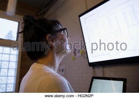 La rédaction de plans d'architecte féminin numérique sur ordinateur portable à écran de télévision Banque D'Images