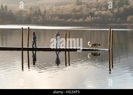 Deux personnes à pied avec un chien sur une jetée en bois ou d'amarrage sur Derwentwater Keswick Cumbria Uk dans Banque D'Images