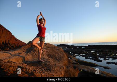 Jeune femme en posture de l'arbre, sur la côte Banque D'Images