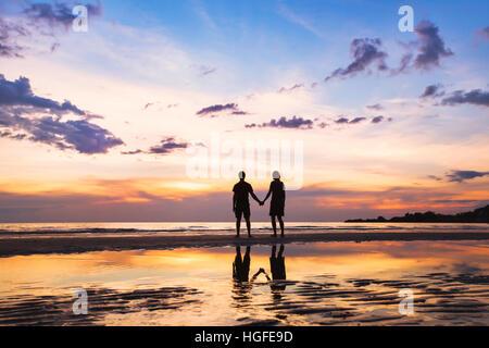 Famille heureuse sur la plage, silhouette de couple at sunset, homme et femme, les relations, l'amour Banque D'Images