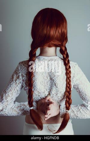 Jeune femme rousse avec deux longues tresses retour à l'appareil photo Banque D'Images