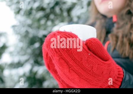 Femme avec des mitaines rouges tenant une tasse avec du thé chaud, café ou chocolat en hiver. Banque D'Images