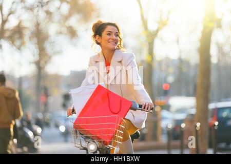 Paris, Woman riding a velib à Paris street Banque D'Images