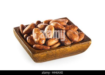 Les fèves de cacao dans un bol en bois isolé sur fond blanc Banque D'Images