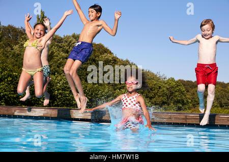 Groupe d'enfants de sauter dans une piscine extérieure Banque D'Images