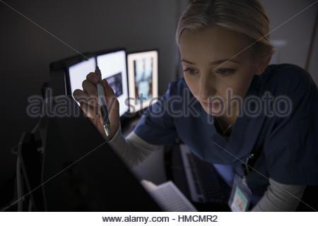 L'accent infirmière de l'examen des radiographies sur les ordinateurs dans l'obscurité médecin Clinique Banque D'Images