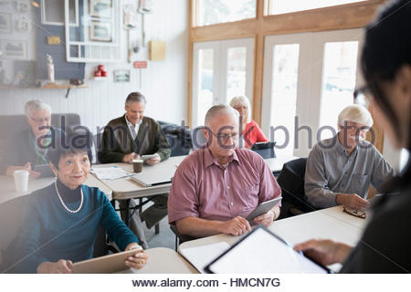 L'enseignant et des aînés à l'aide de tablettes numériques en classe Banque D'Images