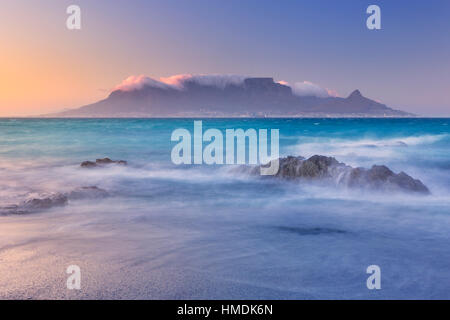 Le lever du soleil sur la Montagne de la table et le cap de la plage de Bloubergstrand. Banque D'Images